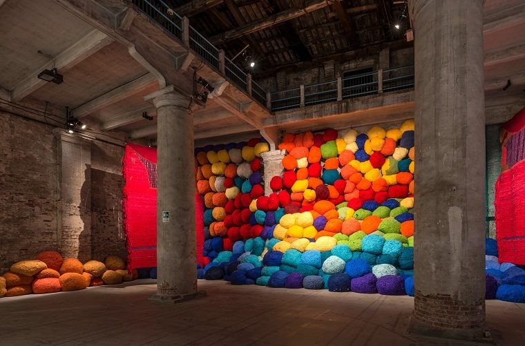 Sheila Hicksdelivers a knockout wall of knitting—all explosive, rumbling colors- at this exhibition of Venice Biennale 2017.
